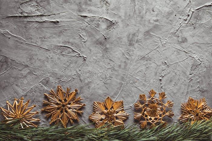 Hausgemachte Strohdekor auf Weihnachtsbaum in der Nähe auf. auf einem grauen Betonhintergrund