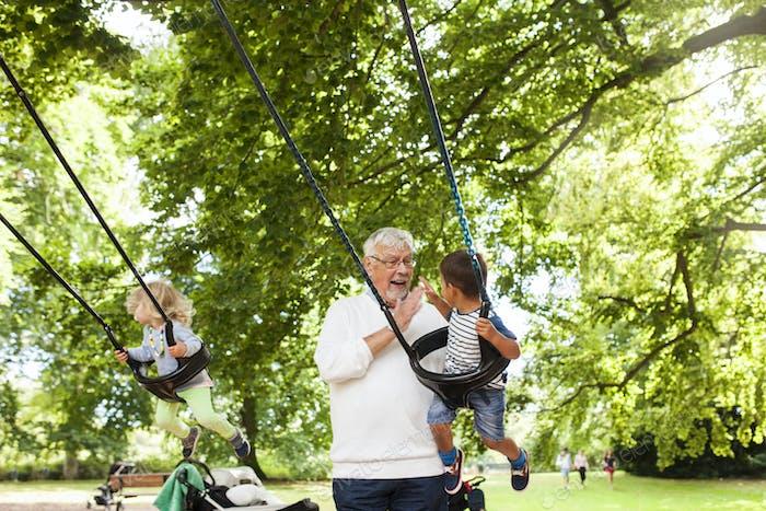 Grandfather swinging grandchildren (2-3) in playground