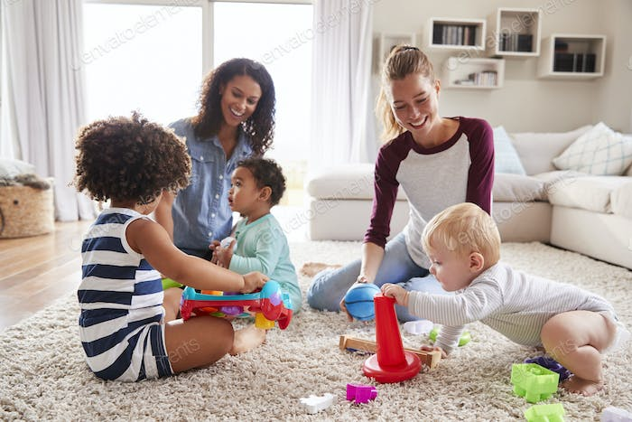 Two friends playing with toddler kids on sitting room floor