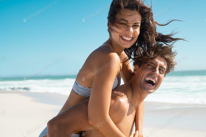 Beautiful woman enjoying piggyback ride at beach
