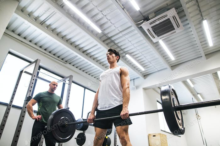 Fit young man with a personal trainer in gym working out, lifting barbell.