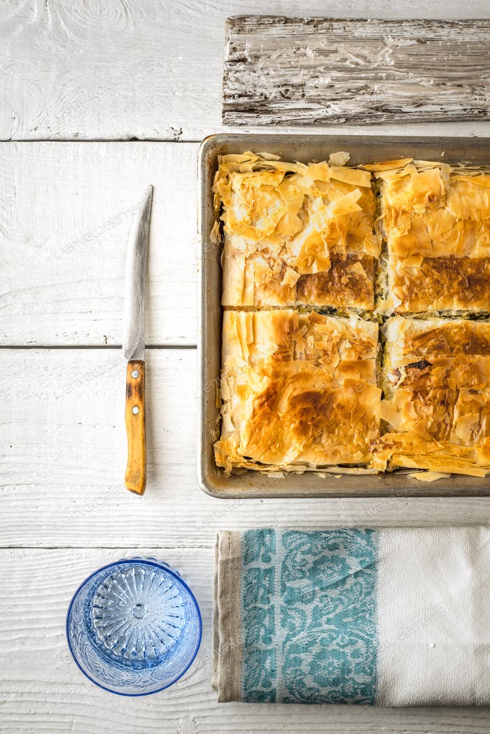 Greek pie spanakopita in the metal pan  with table ware vertical