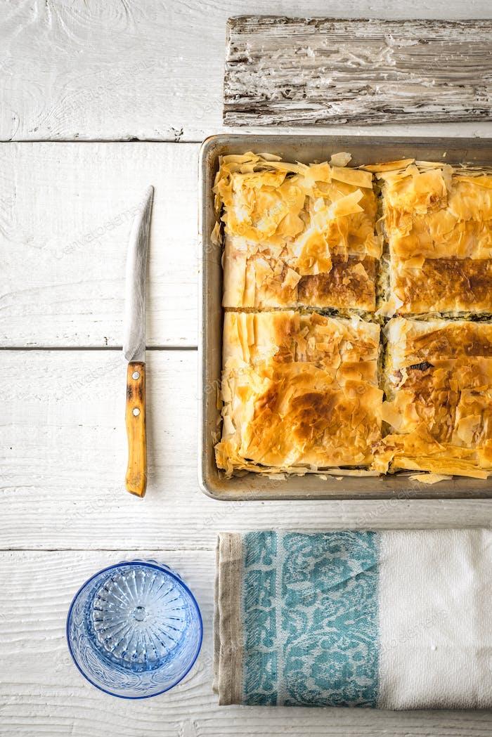 Greek pie spanakopita in the metal pan  with table ware vertical