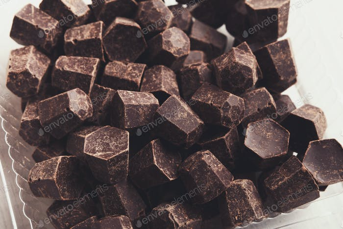 Tasty chocolate chips pile, closeup on white background