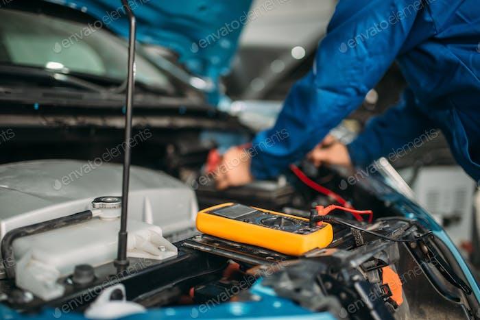 Auto-Elektriker überprüft den Batteriestand