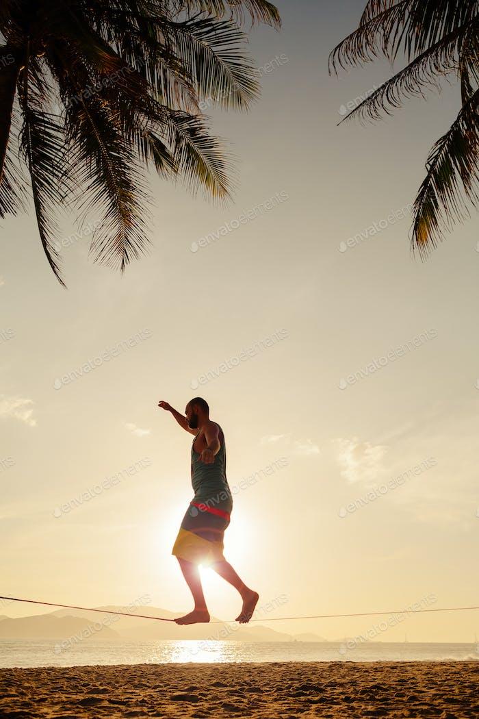 Teenager-Balancing auf Slackline am Strand