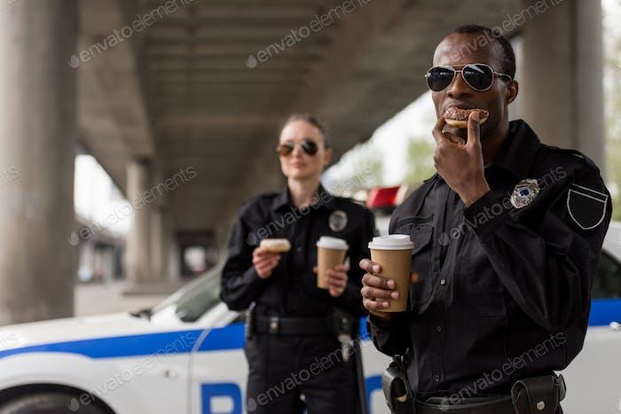 junge Polizisten bei Kaffeepause mit Donuts vor Polizeiauto