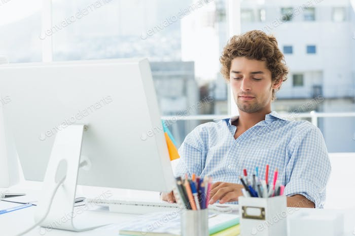 Concentrated casual young business man using computer in a bright office