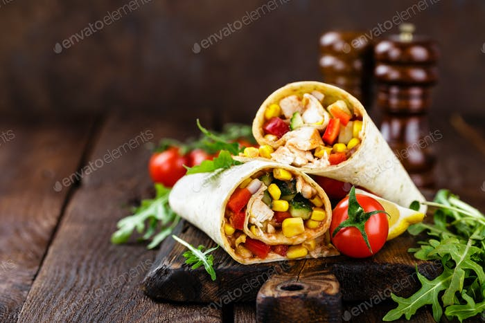 Burritos wraps with chicken meat and vegetables on wooden background