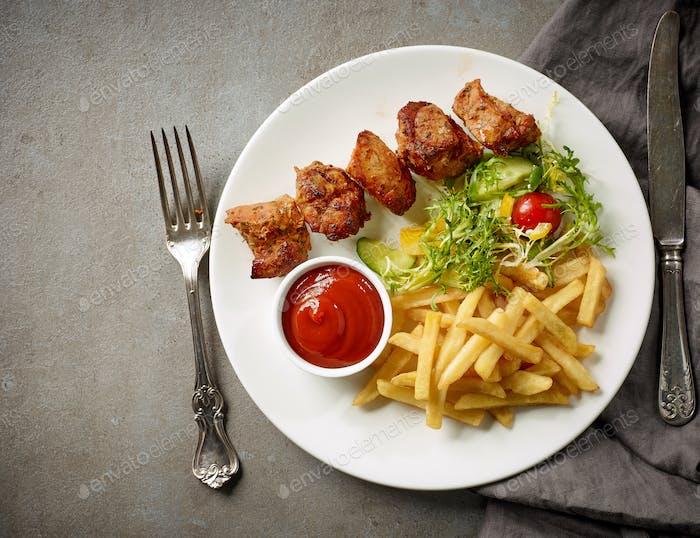 Plate of fried potatoes and pork kebab