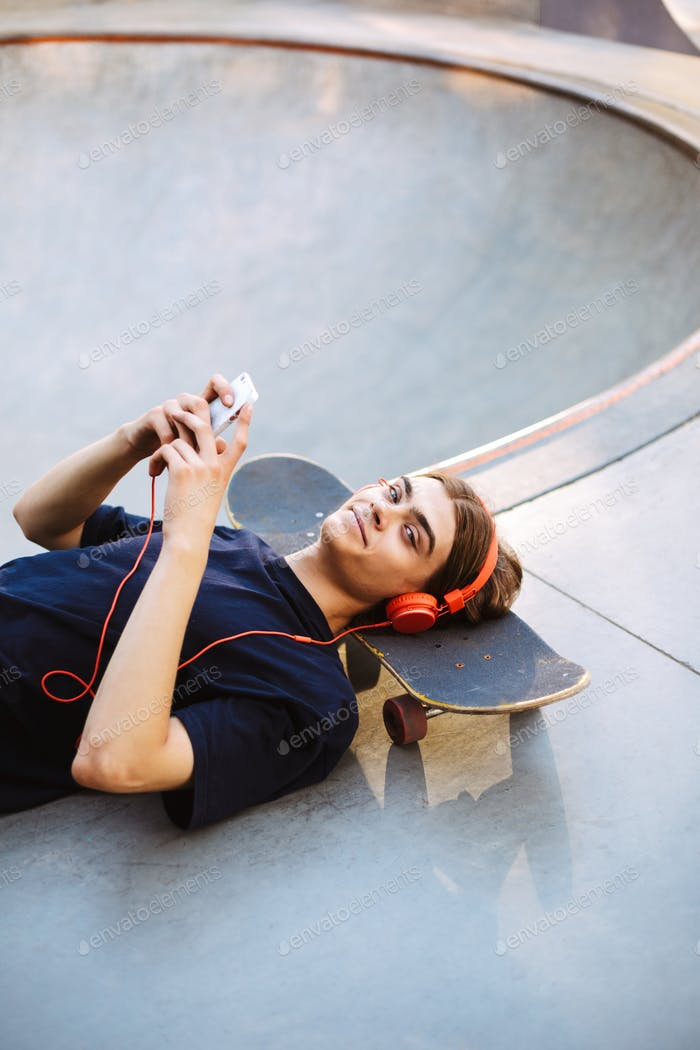 Young guy in orange headphones lying on skateboard with cellphon