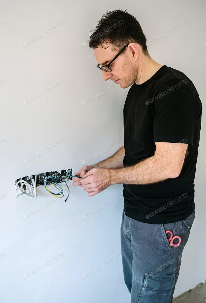 Electricista que trabaja en la instalación eléctrica de una casa
