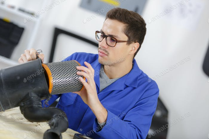 Man fitting filter into plastic tube