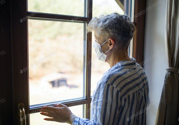 Sad senior woman with face mask indoors at home, corona virus and quarantine concept