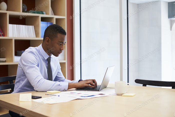Young black businessman working alone in an office, close up