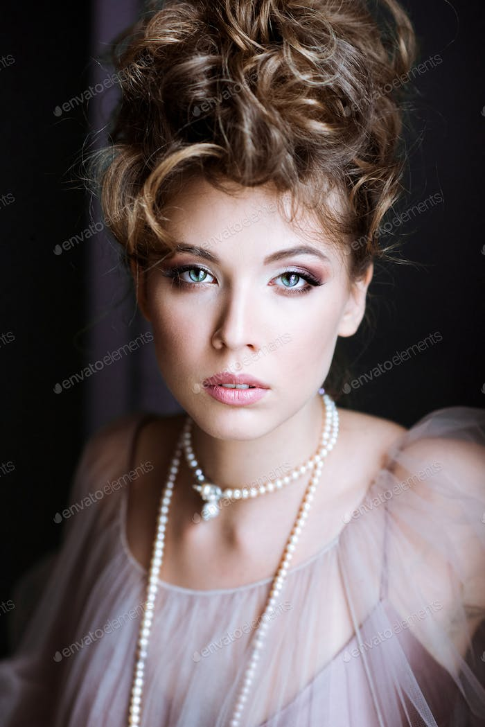 Fashionable female portrait of elegant lady with jewelry indoors
