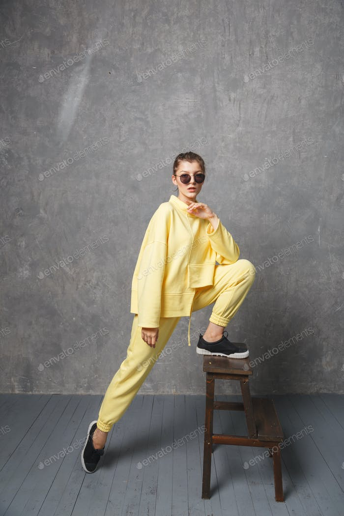 Young woman in yellow sweatshirt and sunglasses on a gray background