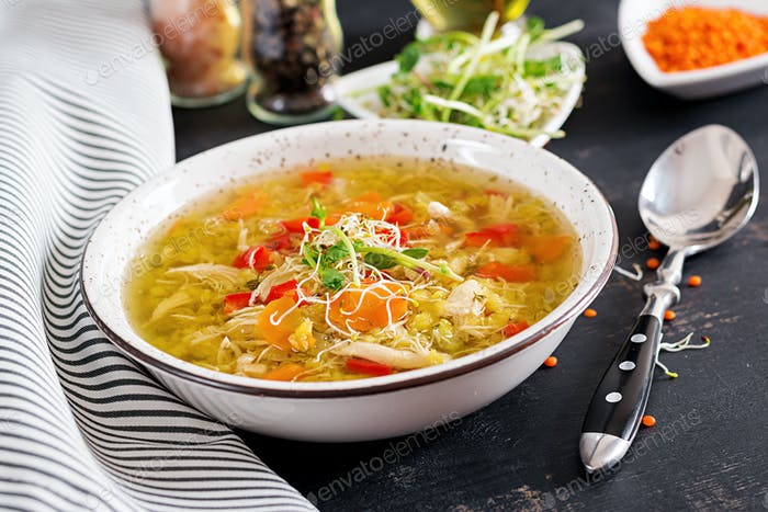 Soup with lentils, carrots, chicken meat, paprika, celery  in a bowl.