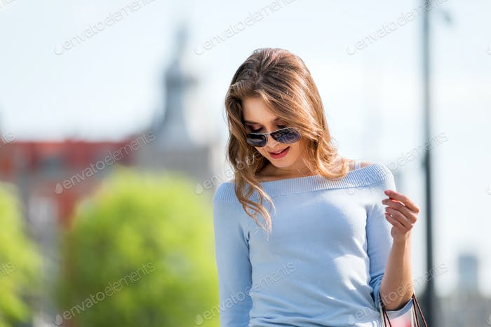Happy young woman with shopping bags walking in the city