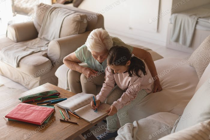 Side view of a grandmother helping her granddaughter with homework in living room at home