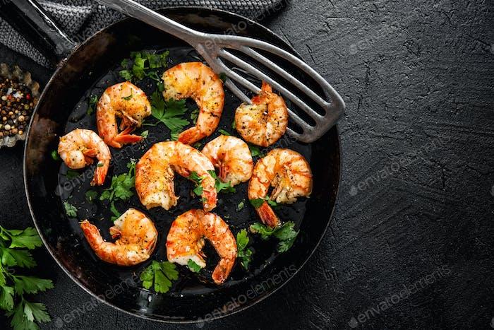 Grilled shrimps on pan on dark background