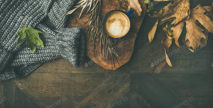 Autumn morning coffee concept with leaves and sweater, copy space