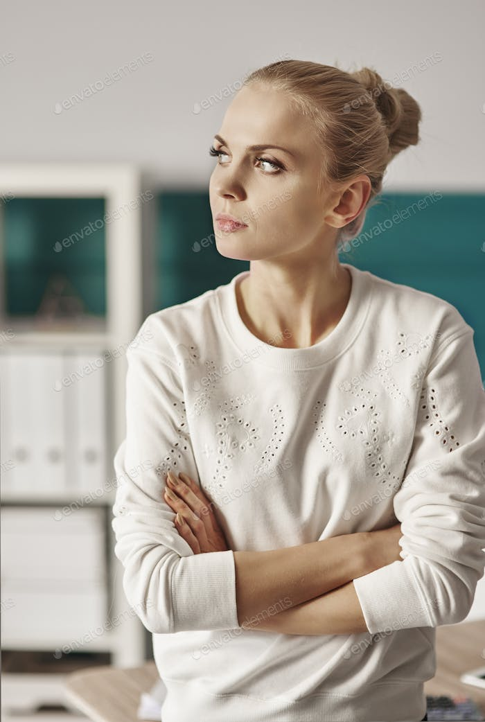 Businesswoman with arms crossed looking through window