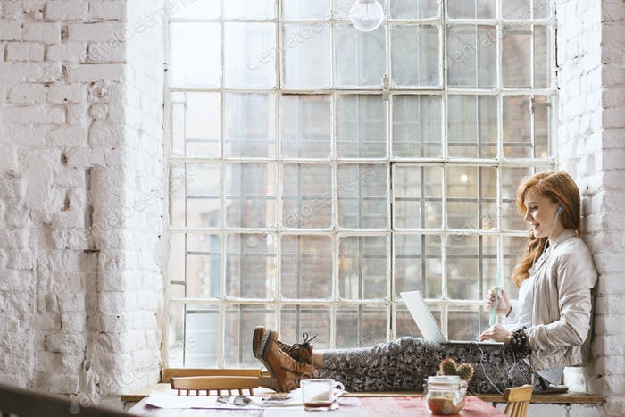 Woman sitting on windowsill with notebook