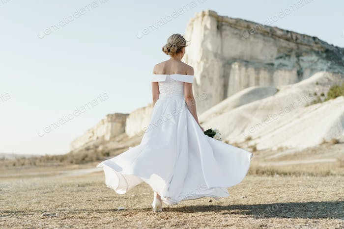 Back view of a bride in a white dress with bare shoulders standing in a field