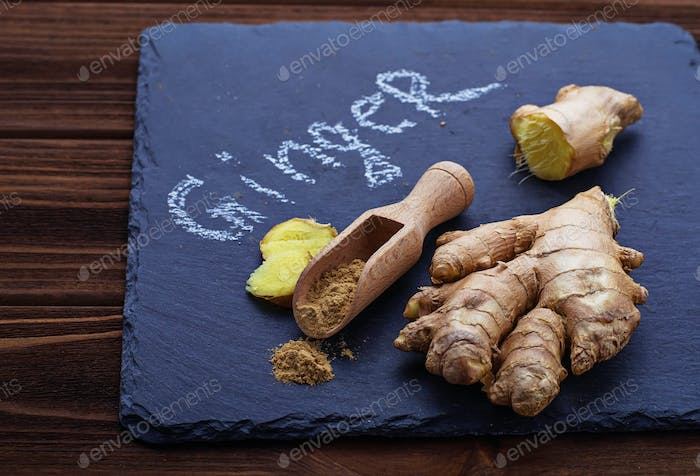 Ginger root and ground ginger on slate