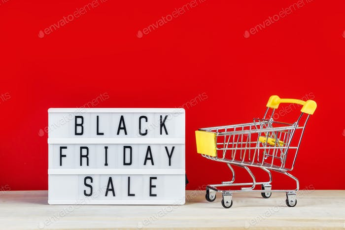 Black Friday sale concept. Mini shopping cart and sign on red background. Banner for advertising.
