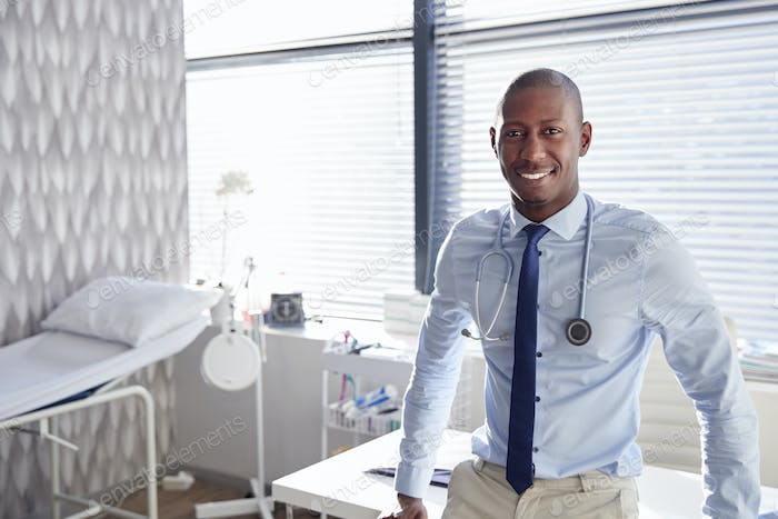 Portrait Of Smiling Male Doctor With Stethoscope Standing By Desk In Office