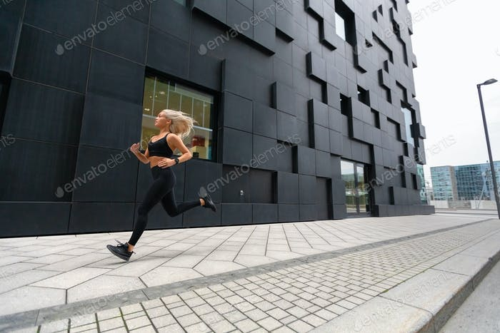 Fast running woman wearing sports top in modern city environment