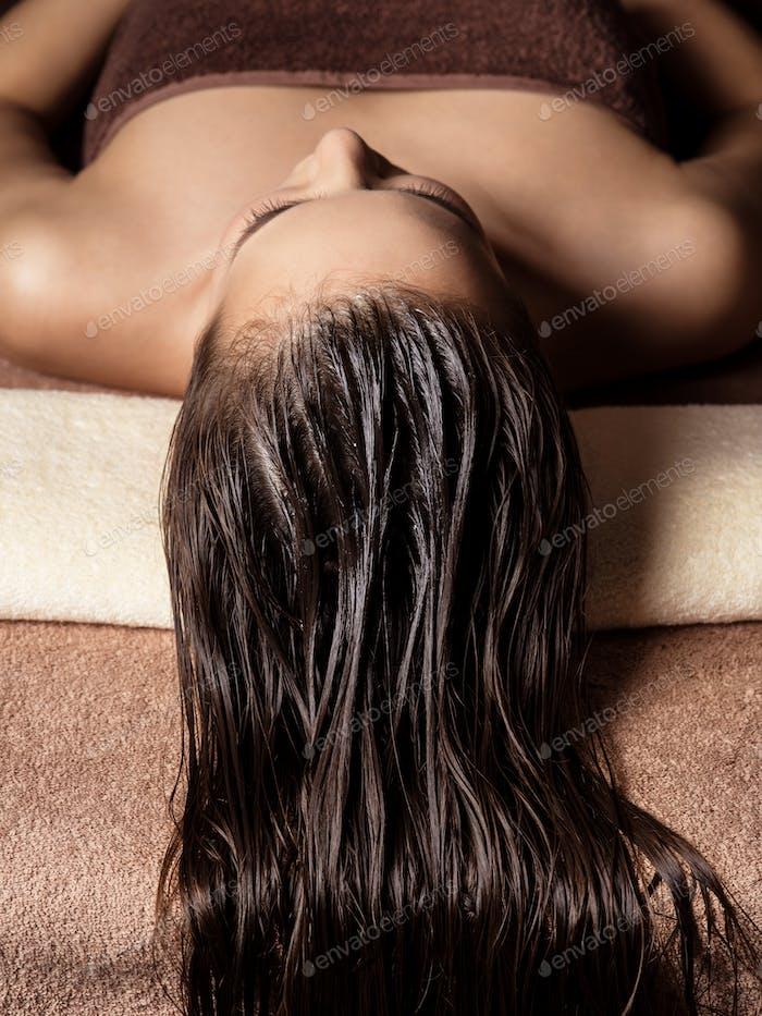 Woman receiving hair care procedure  in spa salon