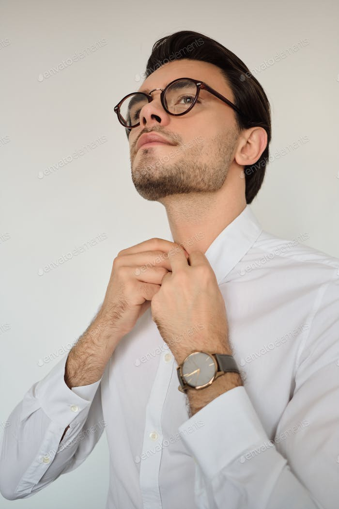 Young handsome brunette man in white shirt and eyeglasses with watch thoughtfully looking aside