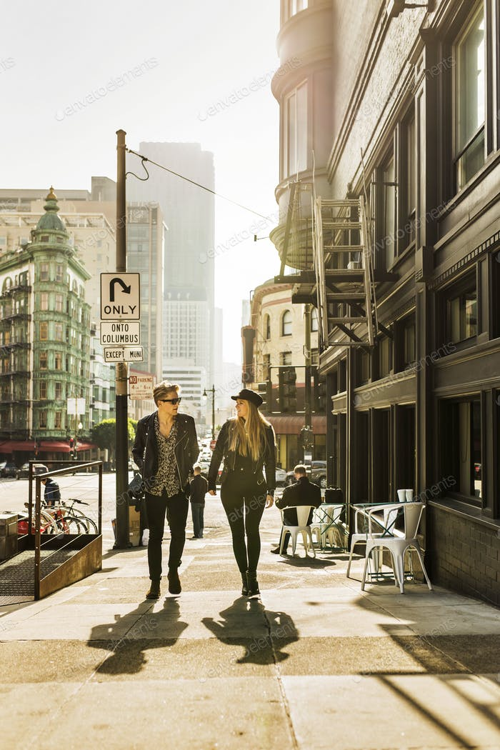 Young man and woman walking in city and talking