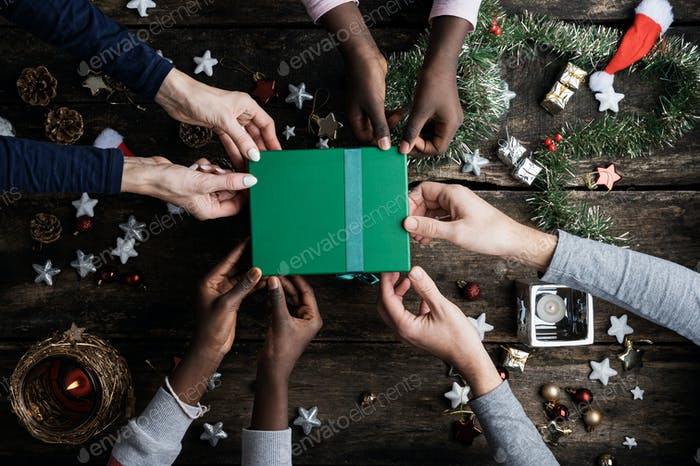 Family of four holding green holiday gift box