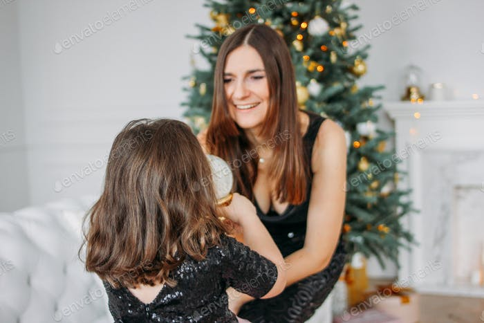 Little girl in dress tutu skirt with mom on background of Christmas tree