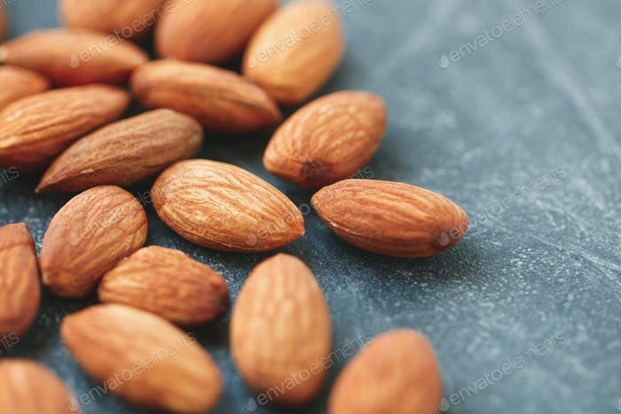 Macro photography of almond nuts over grey background. The concept of healthy and organic food.