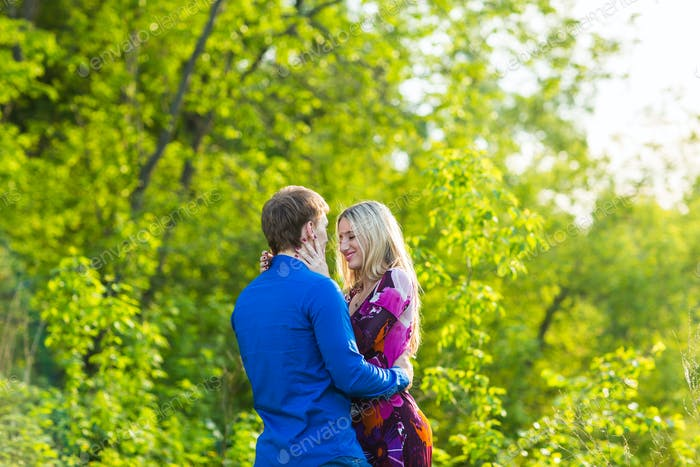 beautiful young couple hugging in the park