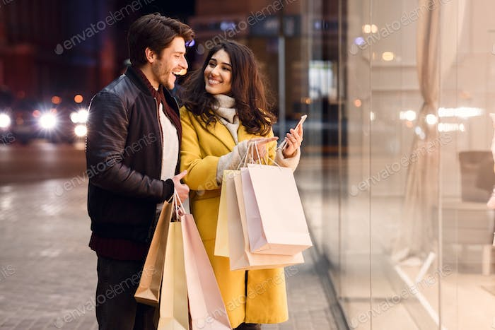 Young couple with shopping bags and smartphone near mall
