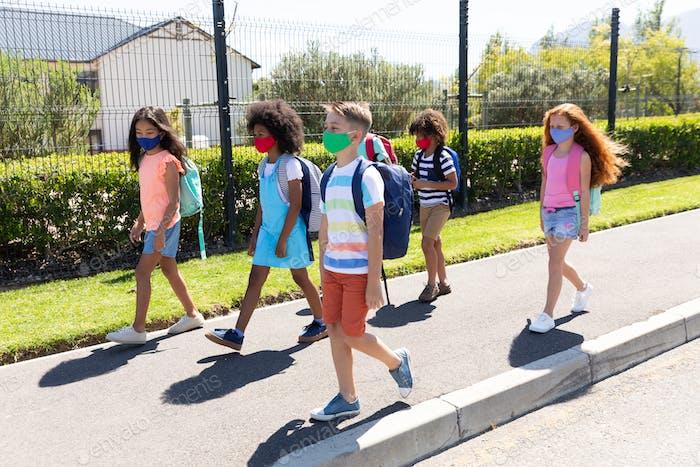Group of kids wearing face masks walking on footpath