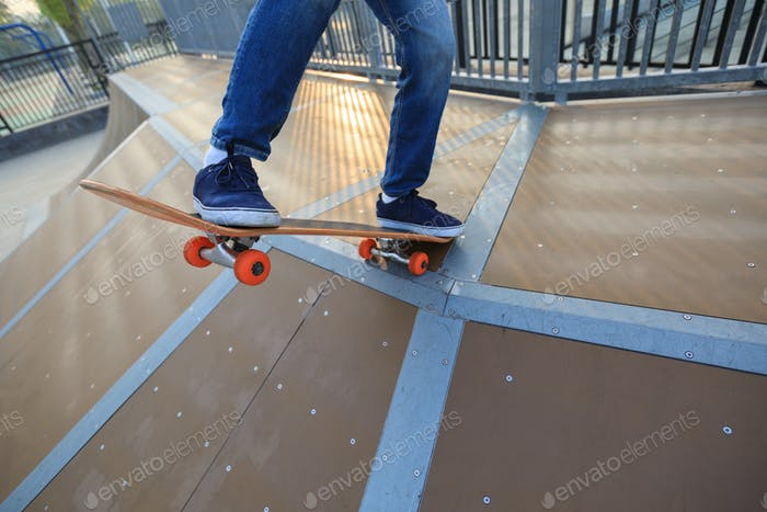 Skateboarder going to descent a ramp at skatepark