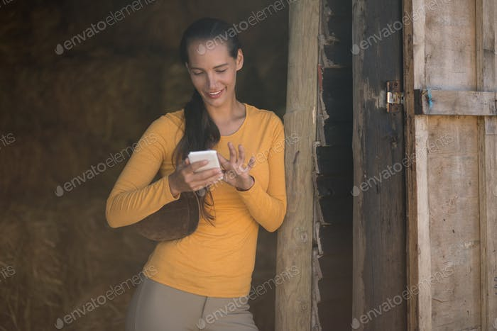 Female jockey using smart phone while standing at stable