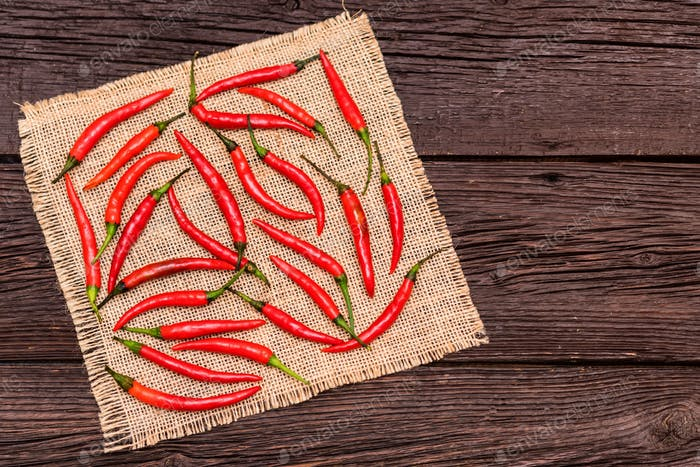 Red chili peppers on cloth and wooden surface