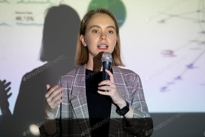 Confident young woman speaking into microphone