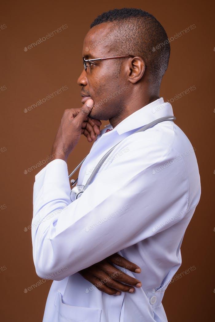 Studioaufnahme von jungen afrikanischen Mann Arzt vor braunem Hintergrund
