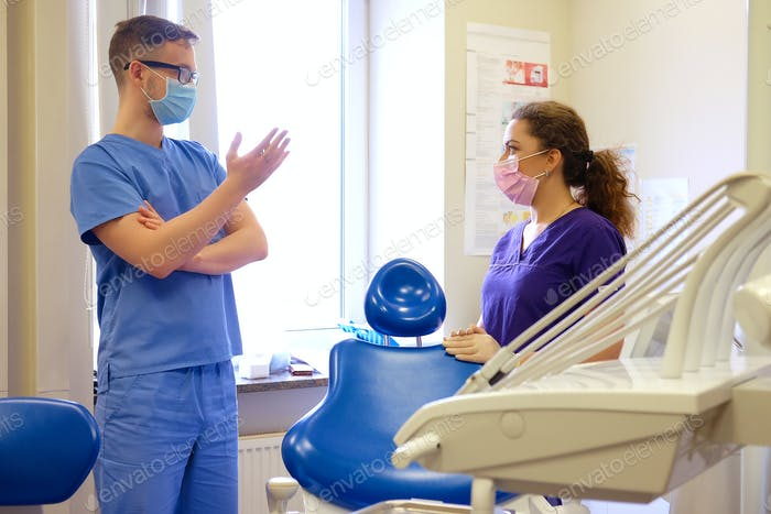 Handsome male dentist speaks with a female assistant at a clinic.