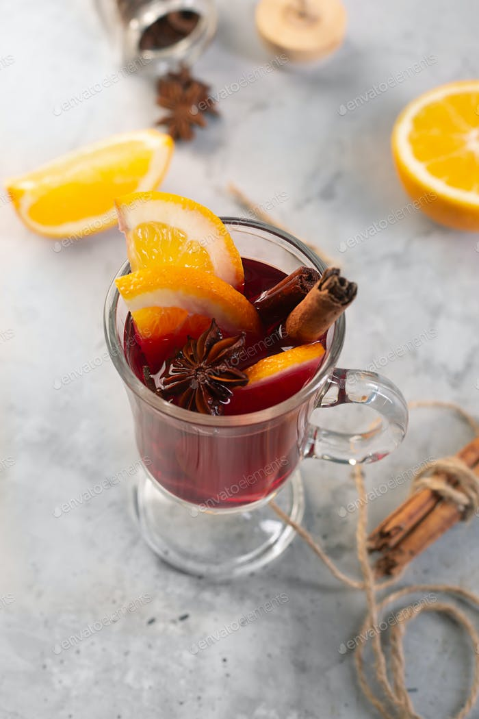Mulled wine with slice of orange and spices on a gray concrete background