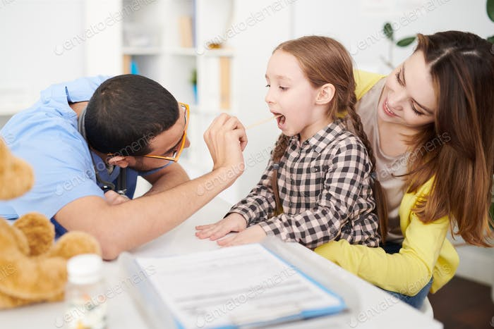 Pediatrician Examining Childs Throat